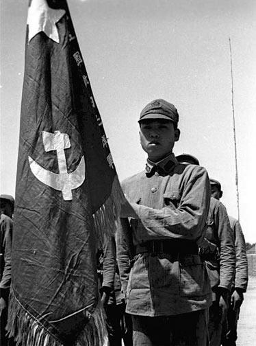 """1934年7月15日,中共发出共赴国难宣言,声称:""""取消红军番号改编为国民革命军,受国民政府军事委员会统辖,并待命出发,担任抗日前线职责""""。图为手持军旗的""""抗日先锋军""""战士。"""