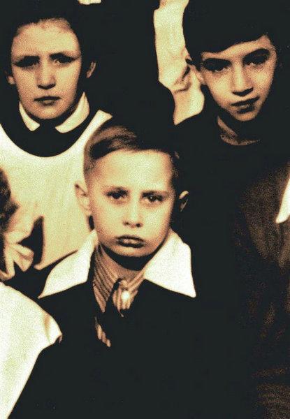 图为1960年在圣彼得堡,8岁的普京和同学站在一起的合影,小小年纪一脸严肃。